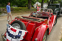 Harris, Barbara and Addison Philpot join the lineup of antiques cars with their red MG for the Gilmanton 4th of July parade on Saturday morning. (Karen Bobotas/for the Laconia Daily Sun)