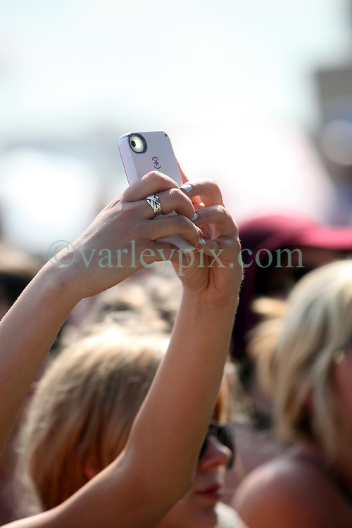 29 April 2012. New Orleans, Louisiana,  USA. <br /> New Orleans Jazz and Heritage Festival. <br /> Young women enjoying the music tweet and text their way through performances.<br /> Photo Credit; Charlie Varley/varleypix.com