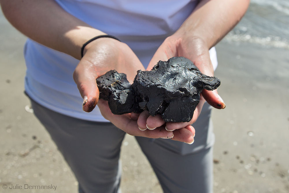 March 31, 2015,  Five years after the BP oil spill, National Wildlife Federation spokesperson,Emily Guidry Schatzel, holds a BP tar ball up on East Grande Terre island, a barrier island in Plaquemines Parish that was hit hard by the BP oil spill in 2010.