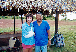 17th November, 2005. Mandeville, Louisiana. <br /> Photo courtesy Denise Leblanc. Denise poses with 'El Doctor,' the day after her horrific attack from a blue marlin in 2000. 'El Doctor,' was the prison medic from a remote prison island colony off the Panamanian coast where denise was taken for immediate medical attention. Here  a heavily sedated Denise poses with 'El Doctor' at a basic dirt air strip where she waits to fly to Panama City for proper medical attention. Denise was stabbed by a Blue Marlin in a freak fishing accident. Denise and her doctors have credited her breast implant with saving her life. <br /> Photo; Charlie Varley<br /> varleypix.com<br /> Photo courtesy; Denise Le Blanc