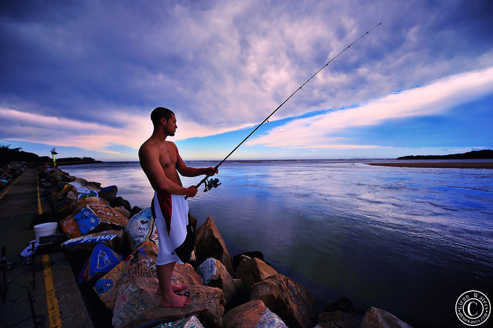 Young man fishing off the V wall rock art gallery at Nambucca Heads NSW Australia. A storm is coming.