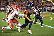 Denver Broncos rookie running back Royce Freeman (28) breaks free from a jersey pull tackle attempt by Kansas City Chiefs linebacker Anthony Hitchens (53) as he runs for a 14 yard touchdown that ties the second quarter score at 10-10 during the NFL week 4 regular season football game against the Kansas City Chiefs on Monday, Oct. 1, 2018 in Denver. The Chiefs won the game 27-23. (©Paul Anthony Spinelli)