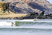 Surfing the waves at Chicama beach, Peru