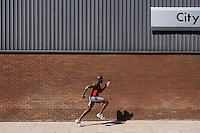 Man running past brick wall with 'city' written on it