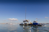 1st March 2014. England, Abu Dhabi Ocean Racing leaves Green Marine by barge on route to Williams Shipping dock, Southampton.