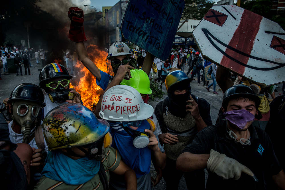 CARACAS, VENEZUELA - MAY 26, 2017:  Anti-government protesters celebrate and burn a police motorcycle that they confiscated during clashes with government security forces. The streets of Caracas and other cities across Venezuela have been filled with tens of thousands of demonstrators for nearly 100 days of massive protests, held since April 1st. Protesters are enraged at the government for becoming an increasingly repressive, authoritarian regime that has delayed elections, used armed government loyalist to threaten dissidents, called for the Constitution to be re-written to favor them, jailed and tortured protesters and members of the political opposition, and whose corruption and failed economic policy has caused the current economic crisis that has led to widespread food and medicine shortages across the country.  Independent local media report nearly 100 people have been killed during protests and protest-related riots and looting.  The government currently only officially reports 75 deaths.  Over 2,000 people have been injured, and over 3,000 protesters have been detained by authorities.  PHOTO: Meridith Kohut
