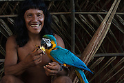 Nama Wani with Blue and Yellow Macaw pet (Ara ararauna)<br /> Bameno Community. Yasuni National Park.<br /> Amazon rainforest, ECUADOR.  South America<br /> This Indian tribe were basically uncontacted until 1956 when missionaries from the Summer Institute of Linguistics made contact with them. However there are still some groups from the tribe that remain uncontacted.  They are known as the Tagaeri & Taromenane. Traditionally these Indians were very hostile and killed many people who tried to enter into their territory. Their territory is in the Yasuni National Park which is now also being exploited for oil.