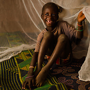 Sainata Ouedraogo under her mosquito net in the village of Bore in the Sanmatenga region of Burkina Faso on 24 February 2014. Mosquito nets greatly decrease the incidence of malaria by reducing the risk of being bitten by the nocturnal Anopheles mosquito, which carries the malaria parasite.