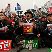 Protestors shout slogans and hold signs decrying the G20, the US-Korean Free Trade Agreement and the South Korean president, Lee Myung-bak, during an anti-G20 protest in Seoul, South Korea, November 11, 2010.