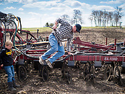"20 APRIL 2020 - BOUTON, IOWA: A farmer jumps off his tiller while his son watches when he was tilling in a field near Bouton. Iowa farmers are prepping their fields for the 2020 season. The relatively mild winter and dry spring has allowed farmers to get into their fields 1 - 2 weeks earlier than last year. Farmers and agricultural workers are considered ""essential"" workers in Iowa and not subjected to the coronavirus restrictions nonessential workers are. Farmers usually work by themselves, and social distancing guidelines have not impacted them as much as it has workers in Iowa's cities.    PHOTO BY JACK KURTZ"