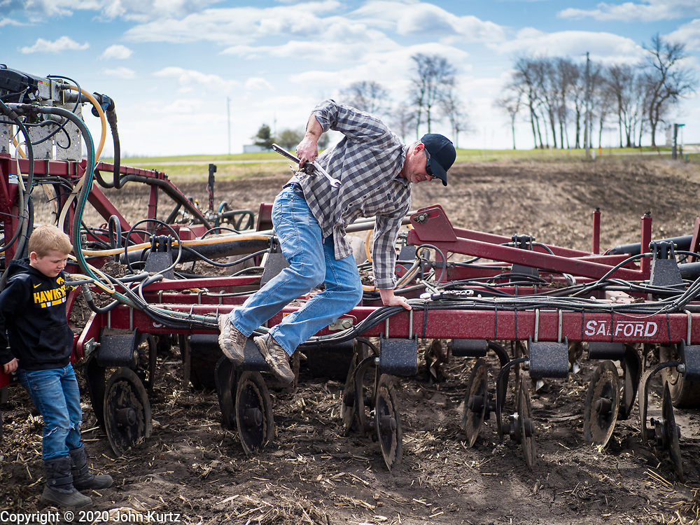 """20 APRIL 2020 - BOUTON, IOWA: A farmer jumps off his tiller while his son watches when he was tilling in a field near Bouton. Iowa farmers are prepping their fields for the 2020 season. The relatively mild winter and dry spring has allowed farmers to get into their fields 1 - 2 weeks earlier than last year. Farmers and agricultural workers are considered """"essential"""" workers in Iowa and not subjected to the coronavirus restrictions nonessential workers are. Farmers usually work by themselves, and social distancing guidelines have not impacted them as much as it has workers in Iowa's cities.    PHOTO BY JACK KURTZ"""