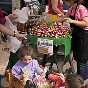 Two children sit in red wagon with sack of fresh produce at University District outdoor farmers market, Seattle, Washington<br />