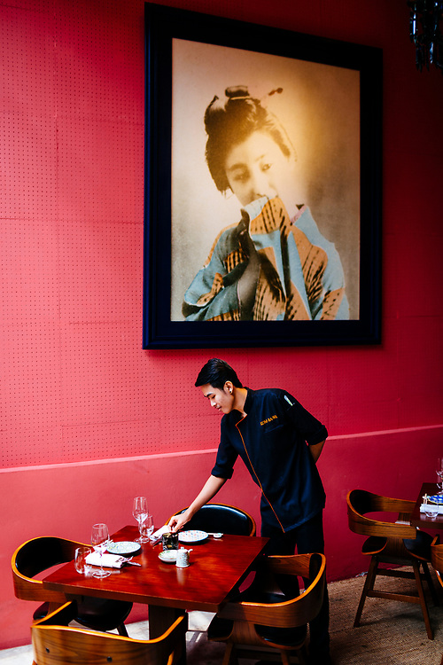 A waiter sets a table at Kom Ba Wa restaurant in Bangkok, Thailand.
