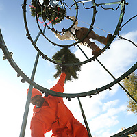 Tyrone Moore hands up tree branches up to Robert Landon as they work with Boyd Yarbrough to put together the Christmas Tree at Fairkpark in Tupelo Tuesday morning.