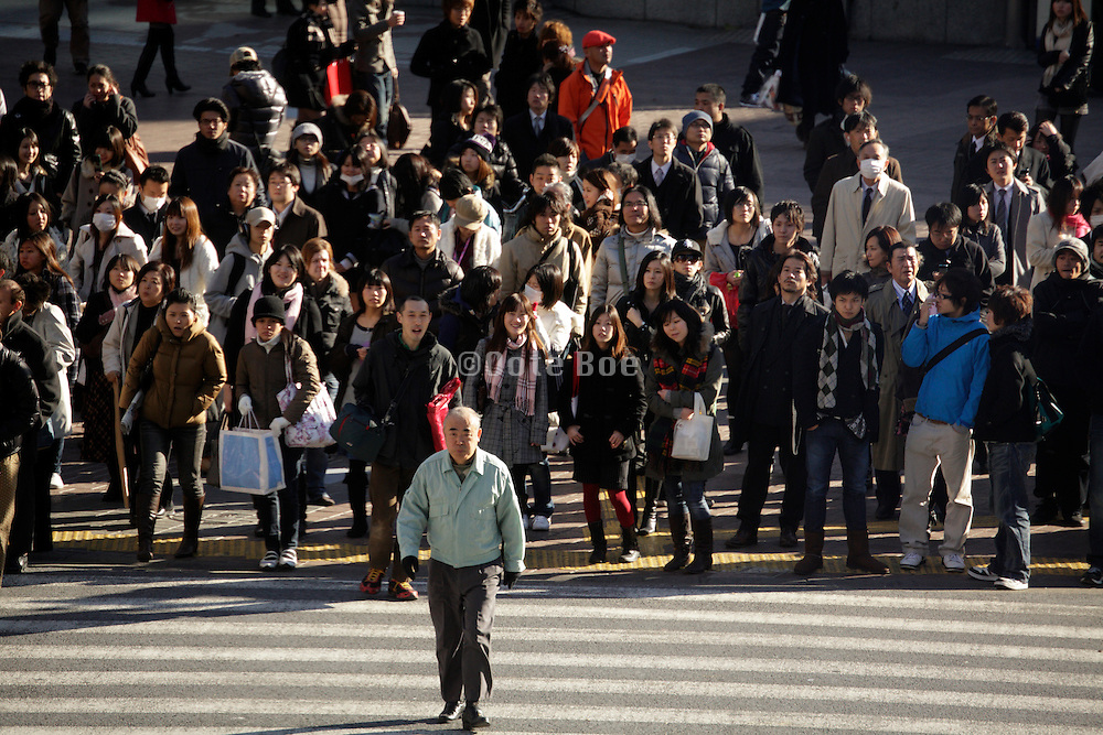 senior man crossing while other people wait for the green light Shibuya  Tokyo  Japan
