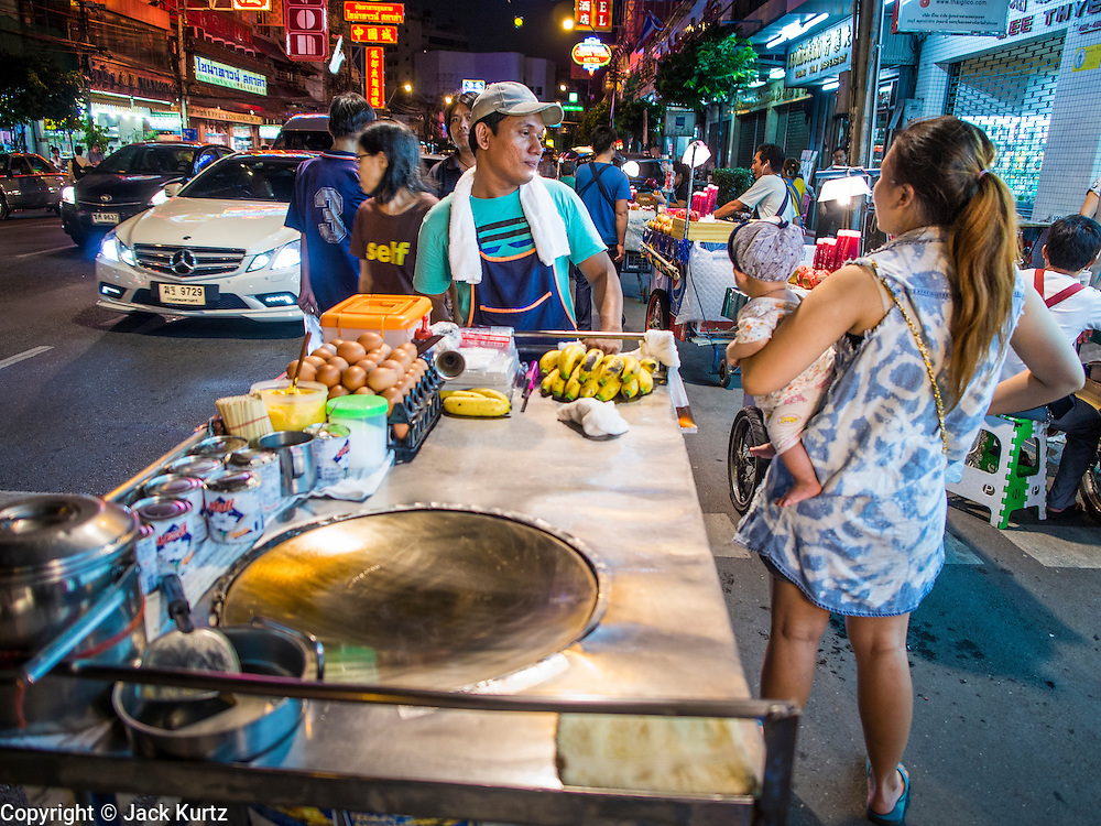 11 SEPTEMBER 2013 - BANGKOK, THAILAND:  A roti (a type of Malaysian fried flat bread very popular in Thailand) talks  to a woman on Yaowarat Road in the Chinatown section of Bangkok. Thailand in general, and Bangkok in particular, has a vibrant tradition of street food and eating on the run. In recent years, Bangkok's street food has become something of an international landmark and is being written about in glossy travel magazines and in the pages of the New York Times.        PHOTO BY JACK KURTZ