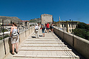 Tourists on famous Stari Most, old bridge, over Neretva River. Mostar. Bosnien. Eastern Europe.