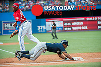 Jul 1, 2014; Toronto, Ontario, CAN; Milwaukee Brewers Left Field Khris Davis dives to make first base watched by Blue Jays First Baseman Edwin Encarcion Milwaukee Brewers and Toronto Blue Jays at Rogers Centre. Mandatory Credit: Peter Llewellyn-USA TODAY Sports