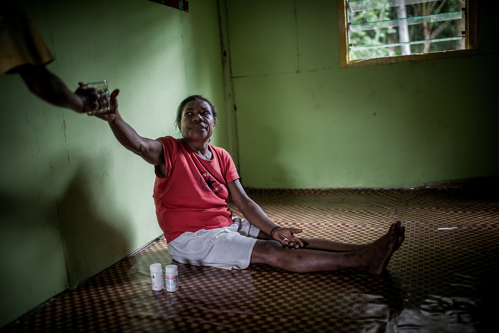 Mama Yuli takes her ARV pills at eight o&rsquo;clock every morning for the last eight years.<br /> <br /> In 2004 Mama Yuli contracted the HIV virus from her husband who later died from AIDS. At her worst point, Mama Yuli was just skin and bones weighing only 22 kilograms (48 pounds). With ARV she is now healthy to work and support her family.<br /> <br /> If taken properly and regularly, ARV has been proven to prolong the survival rate of people living with HIV/AIDS and enables them to live a productive life. The Indonesian government started providing ARV therapies in 2003. In that year only 7 packages of ARV were purchased for all of Papua. Each package cost approximately $5000. Today in Indonesia this vital medication can be obtained at no cost only in Papua but only 12% of those with HIV/AIDS are undergoing ARV therapy.<br /> <br /> Despite these advances, ARV is mostly available only in cities. Collaboration between health facilities in urban centers and staffs in rural areas to make ARV more accessible for patients living in the countryside is still lacking as well as the endorsement of ARV as a legitimate medicine for HIV/AIDS. Sometimes health staff and even educational materials still provide misleading information and perception such as &quot;there is no medicine for HIV/AIDS.&quot;<br /> <br /> As a general practice health personnel often evaluate patients for their adherence in taking their medication and keeping up with appointments before allowing them to undergo ARV therapy. Indigenous Papuans tend to fall short of this assessment and fail to return for their check-up because many of them live too far from the health centers.  At times, they do not fully understand the benefits of ARV medication and the importance of taking them properly due to poor counseling from the health staff.  Also, many of them are unable to keep their appointments or take medication regularly because they still keep their status a secret from their immediate family members or spouse.