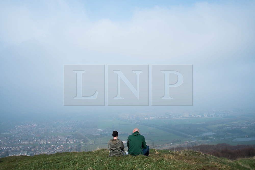 © Licensed to London News Pictures. 29/03/2014<br /> <br /> Eston Hills, Teesside, United Kingdom<br /> <br /> A couple sit and enjoy the views from the top of Eston Nab on Teesside. A community group called the Friends of Eston Hills have recently raised £15000 in just seven weeks to buy the land and return it to public ownership. Today they held a celebration on top of the Nab which is the rocky summit of the Eston Hills to mark the occasion.<br /> <br /> The area will now be returned to public ownership for the first time in hundreds of years and there are plans to raise more funds to create a heritage trail, clean the site up and create a memorial to 375 miners who died when there was an iron mine on the site.<br /> <br /> <br /> Photo credit : Ian Forsyth/LNP
