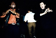 Three men dancing and clapping in a club.