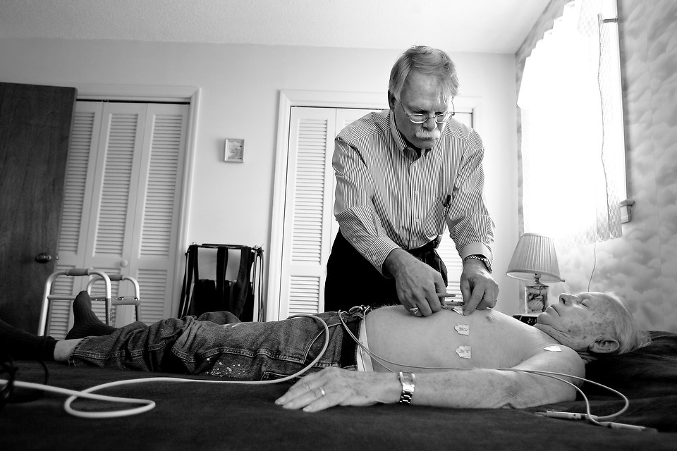 "Dr. Hamrick prepares to perform an electrocardiogram test inside Ray Silbersack's home during a visit in March. Silbersack has an irregular heartbeat that needs monitoring. ""They like being treated as real life people,"" he said. ""And I like being there for them."""
