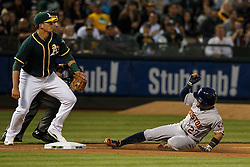 OAKLAND, CA - JULY 19:  Jose Altuve #27 of the Houston Astros slides into third base for a triple in front of Ryon Healy #48 of the Oakland Athletics during the fifth inning at the Oakland Coliseum on July 19, 2016 in Oakland, California. (Photo by Jason O. Watson/Getty Images) *** Local Caption *** Jose Altuve; Ryon Healy