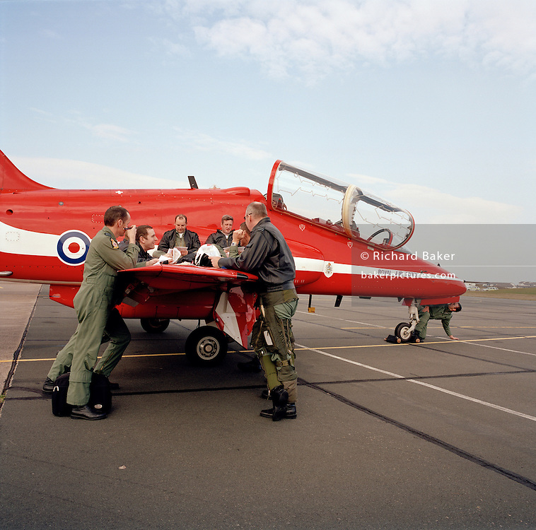 Pilots the 'Red Arrows', Britain's Royal Air Force aerobatic team during pre-flight briefing 'on the wing' before sortie..