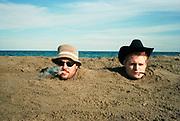 Men buried in sand, UK, 1990s.