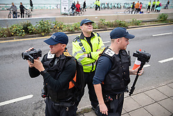"© Licensed to London News Pictures . 22/09/2019. Brighton, UK. Police "" Evidence Gatherers "" carry out overt video surveillance of the protest as it passes in front of the Brighton Centre . Environmental campaigners from Extinction Rebellion highlight the climate emergency and deploy a large red and white lighthouse lightship named "" Greta "" , on Brighton Promenade , during the second day of the 2019 Labour Party Conference from the Brighton Centre . Photo credit: Joel Goodman/LNP"