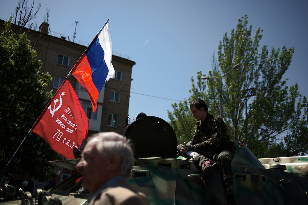 A pro-Russia activist sits atop a armoured personal carrier (APC), captured days earlier from the Ukrainian army, parked in front of Donbass Regional Governmental building in central Donetsk.