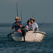 Three fishermen in a small tender on a sunny day on Australia's Great Barrier Reef.