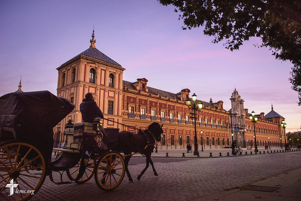 A horse and carriage driver navigates on the street next to the Palace of San Telmo at sunset on Sunday, Nov. 6, 2016, in Seville, Spain.  LCMS Communications/Erik M. Lunsford