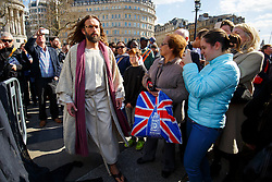 © Licensed to London News Pictures. 25/03/2016. London, UK. Members of public taking pictures of 'The Passion of Jesus' play by the Wintershall Players on Good Friday in Trafalgar Square on 25 March 2016 in London. The Wintershall Players are based on the Wintershall Estate in Surrey and perform several biblical theatrical productions per year. Their production of 'The Passion of Jesus' includes a cast of 80 actors, horses, a donkey and authentic costumes of Roman soldiers in the 12th Legion of the Roman Army. Photo credit: Tolga Akmen/LNP