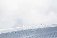 Two hikers / climbers descending from the glaciers and snow fields of Mount Rainier as low clouds rising and fall around them, Mount Rainier National Park, Washington, USA.