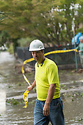 A city worker pulls caution tape across Meeting Street closed by flood waters in historic downtown after Hurricane Matthew passed through causing flooding and light damage to the area October 8, 2016 in Charleston, South Carolina. The hurricane made landfall near Charleston as a Category 2 storm but quickly diminished as it moved north.