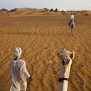 A local guide takes tourists (the photographer) by camel to the pyramids of Meroe, the ancient burial tombs of the Meroe Kingdom. This is one of many  archeaological sites that Sudanese hope will attract tourists.