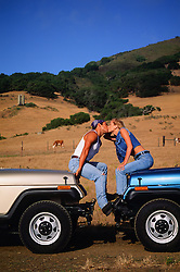couple kissing while sitting on jeeps facing one another in California