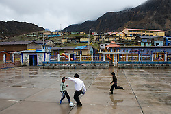Children at play at a community court in Morococha. Several families remain in town resisting the move to the new town.