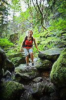An athletic woman scrambling down a rocky path amongst moss covered rocks, Little Si trail, Washington, USA.