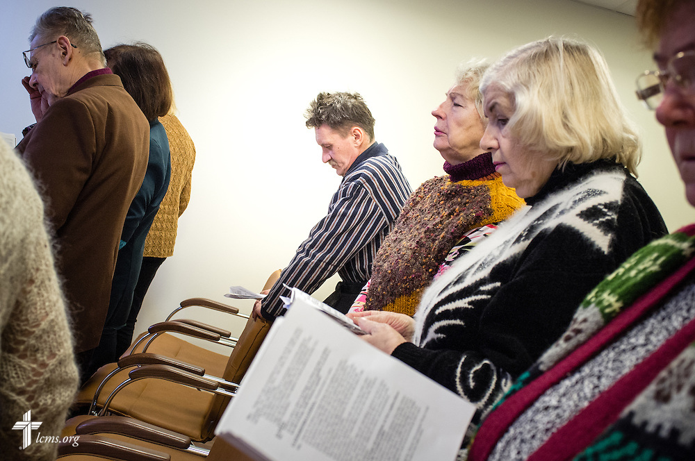 Men and women participate in a Divine Service led by the Rev. Ivo Kirsis (not pictured), a parish pastor in The Evangelical Lutheran Church of Latvia, on Wednesday, Feb. 4, 2015, at a Diaconia Center mercy project site based in a municipal apartment in Riga, Latvia. LCMS Communications/Erik M. Lunsford