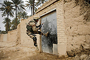 An Iraqi soldier tries to kick open a gate during a cordon and search for insurgence and weapons caches in Chubinait, Iraq, on Feb. 3, 2007.