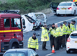 © Licensed to London News Pictures.  16/09/2017; Thornbury, South Gloucestershire, UK. Fatal accident on the M5 motorway. At least 4 people have died. A damaged vehicle can be seen behind the line of police officers. At just before 2.30pm, a lorry travelling southbound went through the central reservation and was in collision with at least two other vehicles in the northbound carriageway. Four people are believed to have died and a number of others have been taken to hospitals in the Bristol area. South Western Ambulance Service have been assisting casualties at the scene and sent 13 resources to the scene, including operations officers, two critical care paramedic teams, four hazardous area response teams (HART) and five double-crewed ambulances. Avon Fire & Rescue Service sent six appliances and its Major Rescue Tender to the scene. Picture credit : Simon Chapman/LNP