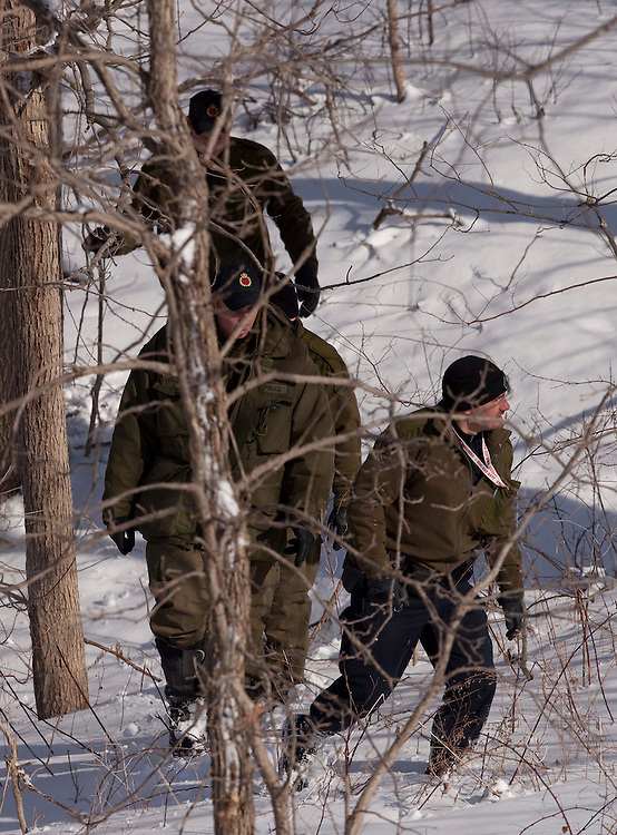 Ontario Provincial Police officers search Sunday, March 6, 2011, for a missing 10 year old girl who fell through the ice Saturday in a creek behind her home near Melborne Ontario.<br /> THE CANADIAN PRESS/ Geoff Robins