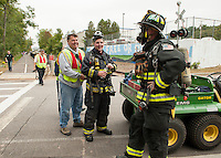 "Laconia Fire Chief Kenneth Erickson adjusts Firefighter Rick Hewlett's oxygen tank along with Dennis Comeau as they join in the 3 mile ""Fun Walk"" wearing full protective gear weighing approximately 60 lbs. on Saturday mornings WOW Fest 2012.  (Karen Bobotas/for the Laconia Daily Sun)"