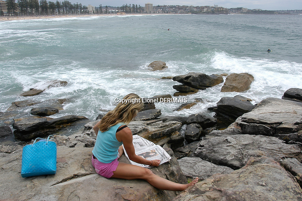 Woman reading the paper on the rocks near Manly beach, Sydney, Australia. January 2nd-11th 2007