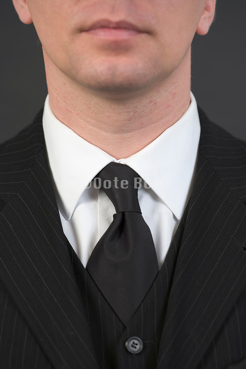 detail of a person in traditional jacket with vest and tie