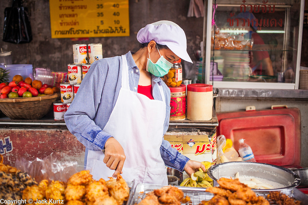 "26 SEPTEMBER 2012 - BANGKOK, THAILAND:  A vendor fries banana fritters in Khlong Toey Market in Bangkok. Khlong Toey (also called Khlong Toei) Market is one of the largest ""wet markets"" in Thailand. The market is located in the midst of one of Bangkok's largest slum areas and close to the city's original deep water port. Thousands of people live in the neighboring slum area. Thousands more shop in the sprawling market for fresh fruits and vegetables as well meat, fish and poultry.    PHOTO BY JACK KURTZ"