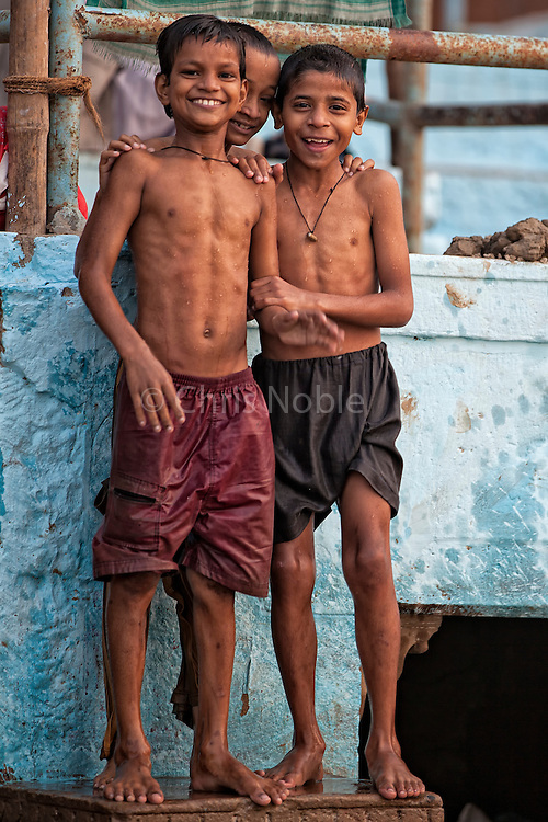 Three boys about to jump into the Ganges River in the holy city of Varanasi, India