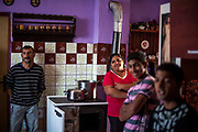 """Pavel (37, left) and family members and friends listening and singing with a Gospel band rehearsing inside a house at the Roma part at the district """"Podsadek"""". The town of Stara Lubovna has a population of 16350, of whom 2 060 (13%) are of Roma origin. The majority of Roma live in the Podsadek district, where 980 (74%) out of 1330 inhabitants are Roma."""